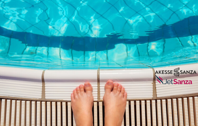 Feet of a young woman standing at the swimming pool