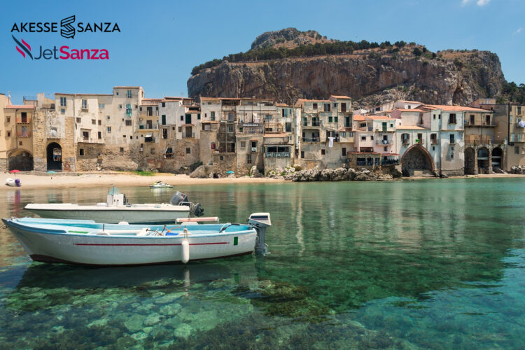 Two dinghy boats in the transparent emerald green water of the small port at the city beach in the old town of Cefalu near Palermo in Sicily with crooked houses in typical waterfront architecture.